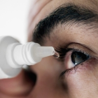 Man applying eye drops into eye, extreme close-up